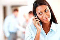 Happy businesswoman talking on cellphone with colleagues blurred in back