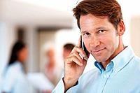 Smart businessman using cellphone with colleagues standing in background