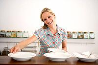 Woman in Kitchen Setting Out Bowls