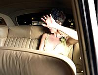 Woman in Limousine Avoiding Photograph