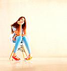 Full length of pretty young girl sitting on chair and daydreaming _ copyspace