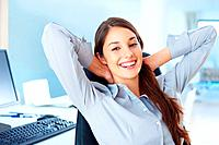 Portrait of happy female executive sitting on office chair and relaxing with hands behind head