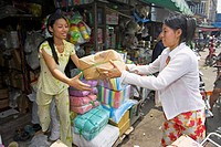 Young women pass packages stocking stall Binh Tay Market Cholon Ho Chi Minh City Vietnam