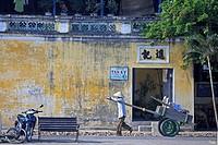Man in conical hat pulls hand cart along street Hoi An historic town mid Vietnam