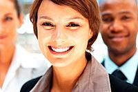 Closeup view of pretty executive smiling with colleagues in background