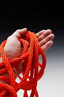 hand clutching orange colored rope
