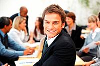 Successful business man smiling with colleagues having meeting in background