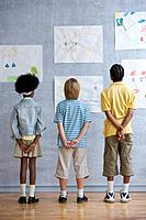 Three Children Looking at Child´s Drawings