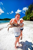 young mother with little child on tropical beach holding a crab to the camera