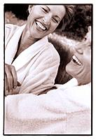 Middle Aged Daughter and Senior Mother Wearing Bathrobes and Laughing