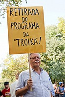 Man carries a sign stating 'withdrawal from the Troika program' in the demonstration against the IMF, the Troika, the Austerity Plan and for the defen...