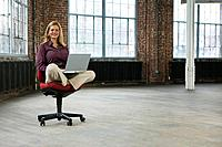 Businesswoman Using Laptop in Empty Office