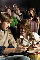 Teenage Couple Texting at the Movies