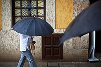 Two black umbrellas in a village street