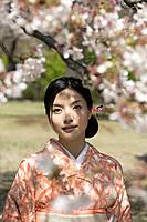 Woman in Traditional Dress Under Cherry Tree