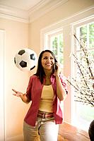 Woman Using Cell Phone and Tossing Soccer Ball