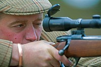 deer stalker hunting reed deers aiming with his gun, United Kingdom, Scotland, Cairngorms National Park