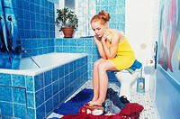 Teenage Girl Sitting next to Bathtup