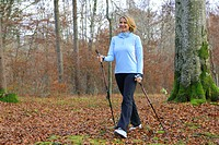 blond woman nordic walking in an autumn forest, Germany