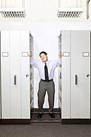 Businessman Trapped Between File Cabinets