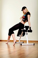 girl sitting on fitness machine
