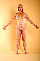 Full length of naked middle_aged woman standing with arms outstretched