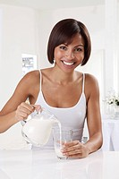 Woman Pouring Milk Into Glass