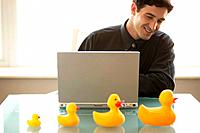 Smiling Businessman with Laptop and Rubber Ducks