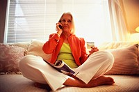 Senior Woman on Sofa Using Cell Phone