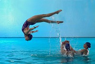Synchronized Swimmer Performing Back Flip in Pool