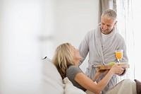 Man bringing wife breakfast in bed