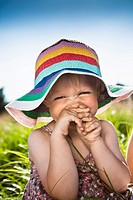 Toddler girl wearing sunhat in grass