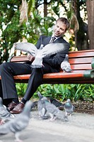Businessman feeding pigeons in park