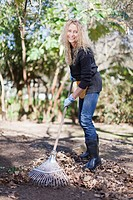 Smiling woman raking leaves outdoors