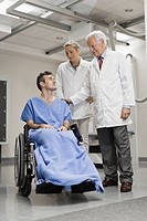Doctors talking to patient in wheelchair