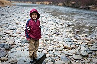 Young Filipino boy 4_5 years standing on river rocks along creek.