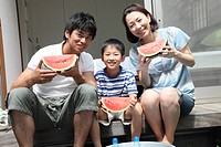 Family holding pieces of watermelon at verandah