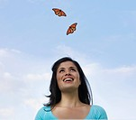A young woman looks up at two monarch butterflies