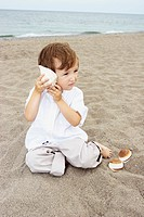 Young Boy Sitting on a Beach Listening to Seashell, Toronto, Ontario