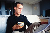 Man working with coffee in bedroom