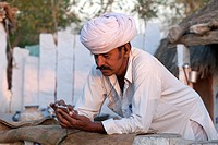 India, Rajasthan, Jodhpur, Village man listening to mp3 player through headphones
