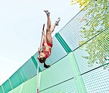 Athlete vaulting over wire fence