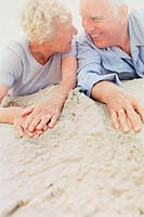 Laughing senior couple lying on the beach
