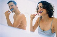 Couple in bathroom, brushing teeth together