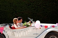 Newlyweds leaving for honeymoon in vintage car
