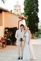 Portrait of newlyweds, groom holding vintage camera