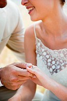 Newlyweds looking at wedding ring, close up