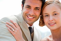 Bride wearing wedding ring with hand on groom's shoulder