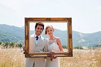 Newlyweds holding vintage picture frame (thumbnail)