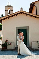 Newlyweds outside church, embracing (thumbnail)